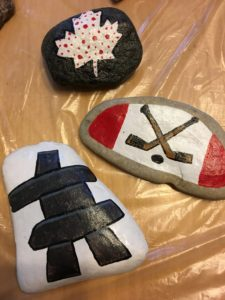 Photo of three painted rocks: hockey sticks, inukshuk and white maple leaf with red polka dots. Photo courtesy Purple Door Creative.