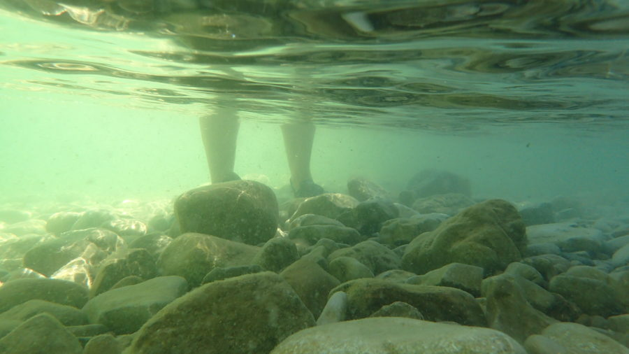 Feet and legs in the water of rocky lake bottom. Photo courtesy Purple Door Creative